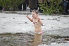 L'enfant se baignent en rivière en hiver. Vacances religieuses d'épiphanie Images libres de droits
