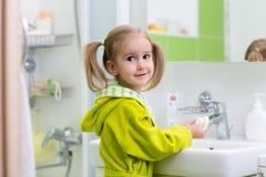 L'enfant se lave les mains à la salle de bains Mains de lavage de fille avec du savon photographie stock
