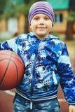 L'enfant se tient avec l'extérieur et tient un basket-ball dans ses mains, regards à la caméra et sourires vertical photographie stock