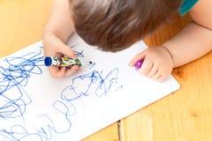 L'enfant se trouvant sur le plancher et dessine Photo stock