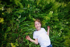 L'enfant se trouve sur l'herbe Photo stock