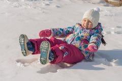 L'enfant se trouve sur la neige Photographie stock libre de droits