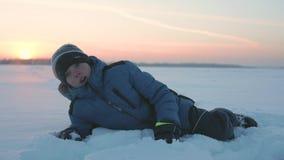 L'enfant se trouve sur la neige et regarde le coucher du soleil Stationnement de l'hiver banque de vidéos