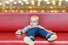 L'enfant se trouve sur le divan au centre commercial ou au mail Petit garçon fatigué pendant les achats avec des parents images stock