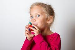L'enfant souffle dans le sifflement Photo stock