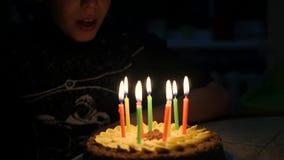 L'enfant souffle les bougies sur le gâteau dans votre anniversaire 10 ans banque de vidéos