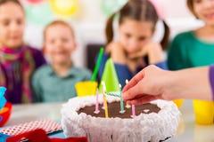 L'enfant sur la fête d'anniversaire a préparé les bougies de soufflement sur le gâteau, selecti Photos libres de droits