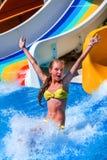 L'enfant sur la glissière d'eau à l'exposition d'aquapark manient maladroitement  Photo stock