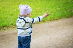 L'enfant sur la route regarde et montre sa main en avant Image stock