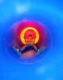 L'enfant sur le terrain de jeu descend dans une grande glissière bleue de tunnel Photographie stock