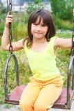 L'enfant sur une oscillation Photos stock