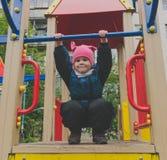 L'enfant surmonte des obstacles jouant sur le terrain de jeu Images stock