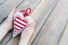 L'enfant tenant le coeur remet dedans une table en bois Photos stock