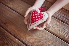 L'enfant tenant le coeur rouge de textile remet dedans une table en bois Photographie stock