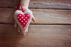 L'enfant tenant le coeur rouge de textile remet dedans une table en bois Images libres de droits