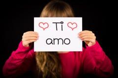 L'enfant tenant le signe avec l'Italien exprime l'AMO de Ti - je t'aime Photographie stock libre de droits