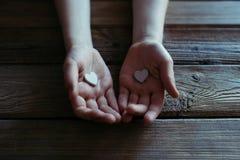 L'enfant tenant les coeurs blancs remet dedans une table en bois Images libres de droits