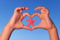 L'enfant tient des mains jusqu'au ciel sous forme de coeur avec des étoiles de mer Mains d'enfant de forme d'amour avec des étoil Image stock