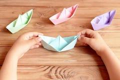 L'enfant tient l'origami se transportent dans des ses mains Pliage de papier d'origami coloré de bateaux sur une table en bois Photographie stock libre de droits