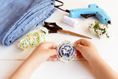 L'enfant tient la fleur de denim de broche dans des ses mains Broche créative de fleur utilisant de vieux jeans image libre de droits