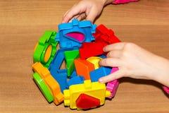L'enfant tient les jouets de blocs constitutifs dans des ses mains et fait le lit Constitutif des blocs joue pour des enfants sur Photos stock