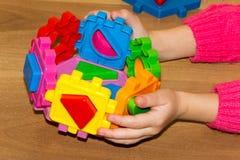 L'enfant tient les jouets de blocs constitutifs dans des ses mains et fait le lit Constitutif des blocs joue pour des enfants sur Photo stock