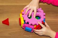 L'enfant tient les jouets de blocs constitutifs dans des ses mains et fait le lit Constitutif des blocs joue pour des enfants sur Photographie stock