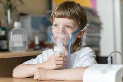 L'enfant tient un inhalateur de vapeur de masque Photo stock