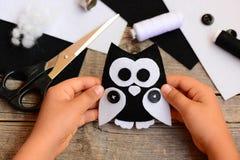L'enfant tient un jouet de hibou de feutre dans sa main Le petit enfant a fabriqué un hibou à partir de le feutre noir et blanc E Image stock