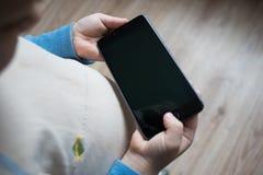 L'enfant tient un téléphone dans sa main Image libre de droits