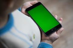 L'enfant tient un téléphone dans sa main avec un écran vert pour Images stock
