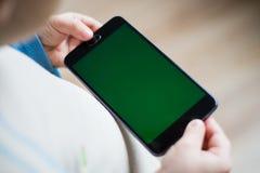 L'enfant tient un téléphone dans sa main avec un écran vert pour Photos libres de droits