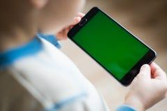 L'enfant tient un téléphone dans sa main avec un écran vert pour Photographie stock libre de droits