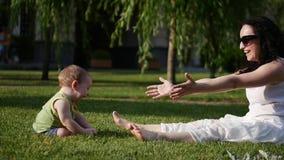 L'enfant tire ses mains du ` s de mère Le bébé prend les premières étapes Pièces de mère avec l'enfant banque de vidéos
