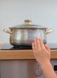 L'enfant touche la casserole chaude sur le fourneau image stock