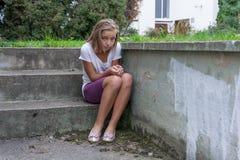 L'enfant triste s'assied sur des escaliers isolés Images libres de droits