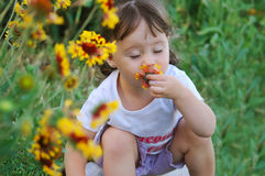L'enfant une fleur sentante Photo stock