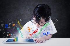 L'enfant utilise le comprimé avec la formule Photographie stock