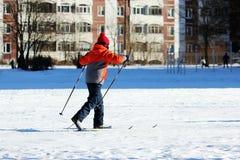 l'enfant va skier sur la cour intérieure de l'école pendant les classes d'éducation physique Photographie stock