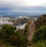 L'enroulement sinueux de route de montagne autour des rochers et de l'amoungst de forêt opacifie Images stock