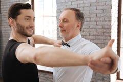 L'enseignement avec plaisir d'instructeur de danse a vieilli l'homme à la salle de bal Photos stock