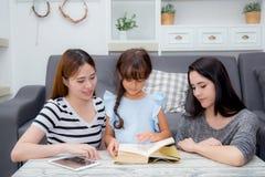l'enseignement heureux de mère, de tante, d'ami et de fille de famille a lu un livre Photographie stock libre de droits