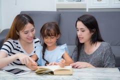 l'enseignement heureux de mère, de tante, d'ami et de fille de famille a lu un livre à la maison Photographie stock libre de droits