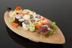 L'ensemble assorti de sushi a servi dans le plat en bois de bateau Image stock