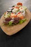 L'ensemble assorti de sushi a servi dans le plat en bois de bateau Photo stock