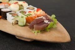 L'ensemble assorti de sushi a servi dans le plat en bois de bateau Photographie stock libre de droits