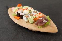 L'ensemble assorti de sushi a servi dans le plat en bois de bateau Photos libres de droits