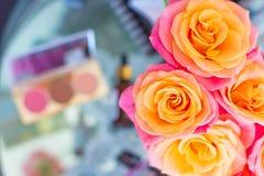L'ensemble cosmétique avec des brosses et les fausses mèches d'oeil avec composent le sac, les roses rose-oranges et l'accessoire image libre de droits