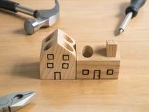 L'ensemble d'outils et la maison en bois faite main jouent. Photographie stock