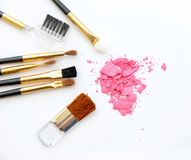 L'ensemble de composent le cosmétique, la brosse, poudre rose sur le fond blanc Image libre de droits